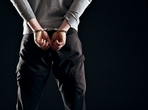 Murderer locked in handcuffs isolated on black