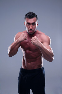 Muscular man boxing over gray background