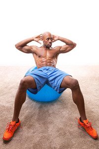 Muscular man doing ab crunches on an exercise ball.