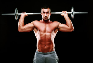 Muscular man doing exercise with barbell over black background