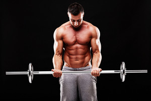 Muscular man lifting barbell over black background