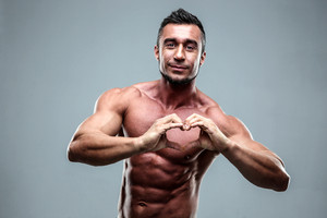 Muscular man making heart symbol with his hands
