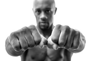 Muscular man of African descent isolated over a white background showing a closeup of his fists and fingers.  Shallow depth of field.