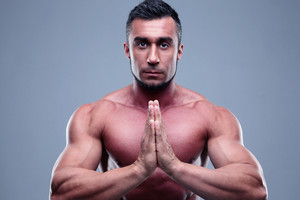 Muscular man praying over gray background