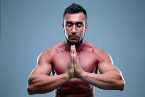 Muscular man praying with closed eyes