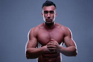Muscular man standing over gray background