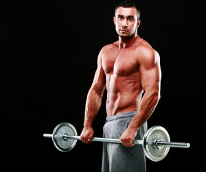 Muscular man standing with barbell over black background