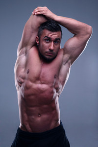 Muscular man stretching his hands over gray background