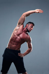 Muscular man stretching over gray background