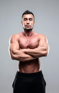 Muscular man with arms folded standing over gray background