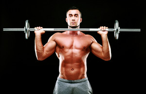 Muscular man working out with barbell over black background
