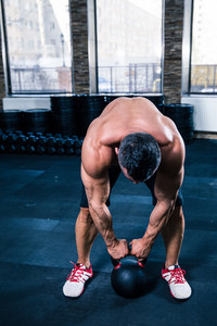 Muscular man workout with kettle ball at gym