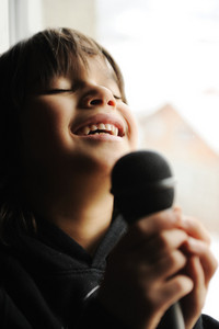 Musician kid singing with microphone