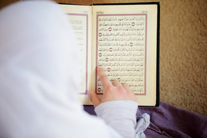 Muslim and Arabic girls reading Koran together in group