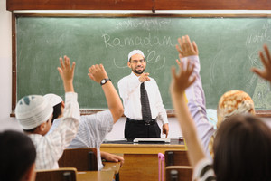 Muslim arabic children with teacher at school