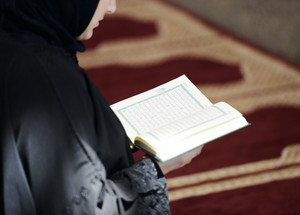 Muslim Arabic woman sitting and reading holy book Koran
