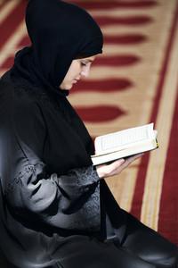 Muslim Arabic woman sitting and reading holy book Koran