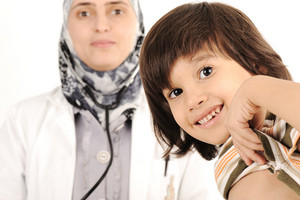 Muslim female doctor in hospital examining a little boy
