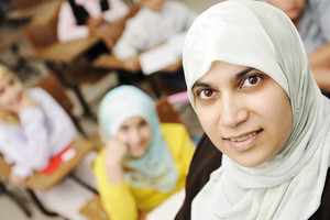 Muslim female teacher in classroom with children pupils (students)