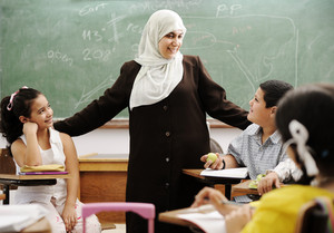 Muslim female teacher with children in classroom in modern school
