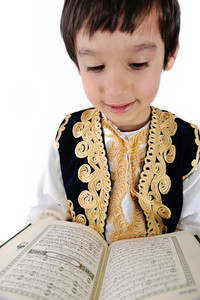 Muslim kid reading holy Quran