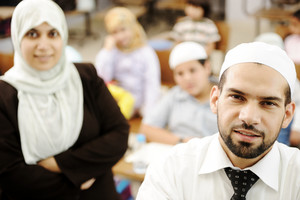 Muslim male and female teachers in classroom with childrens