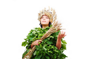 Nice little girl in leafs cloths with wheat hat on head