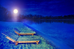 Night landscape with two wooden sunbeds. Bank of lake in the night in autumn.