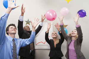 Office people tossing balloons