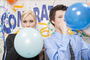 Office staff blowing up balloons