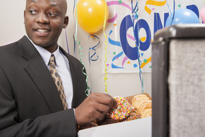 Office worker eating donuts at party