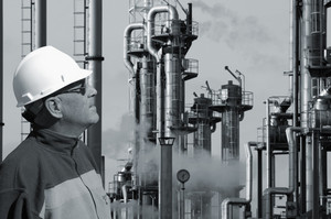oil and gas worker in close-ups, refinery in background
