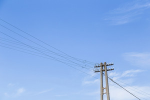 Old electricity post with blue sky