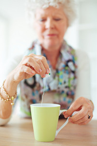 Old lady sitting at home holding and dipping a tea bag