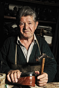 Old man, shoemaker, repairing old handmade shoe in his workshop and looking at the camera
