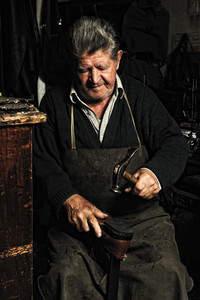 Old man, shoemaker, repairing old handmade shoe in his workshop, hitting with a  hammer