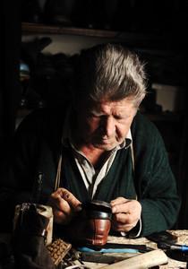 Old man, shoemaker, repairing old handmade shoe in his workshop