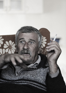 Old man with mustache smoking cigarette while sitting in sofa and speaking