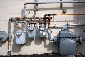 Old natural gas utility pipes and meters in an urban commercial setting.