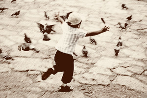 Old photo, kid running after pigeons on street