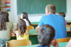 Old pupil in the middle of children in classroom
