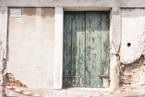 Old vintage wood door with old green wallpaper
