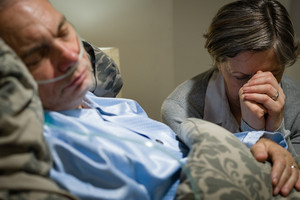 Old wife praying for terminally ill husband lying in coma