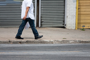 One man walking down the sidewalk along the side of the road.