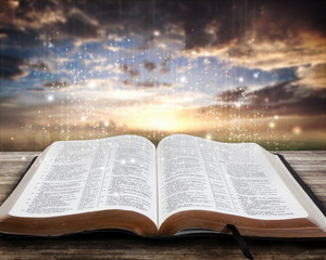 Open glowing Bible on table at sunset