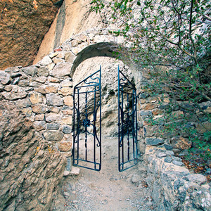 Open iron gate in rock
