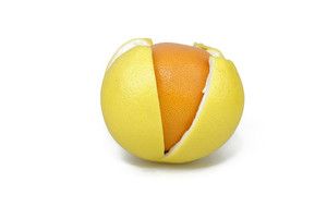 Orange In A Grapefruit Peel On White Background