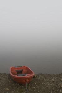 Orange rowboat on a lake shore in thick fog