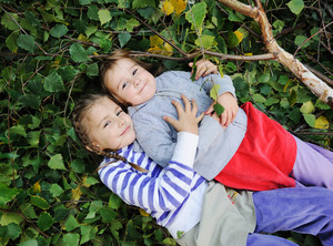 outdoor, happy faces between the leaves of the trees in forest or park