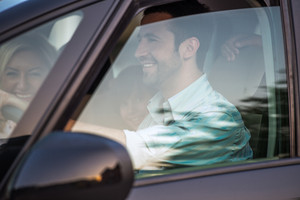 Outside view of smiling couple driving in a car
